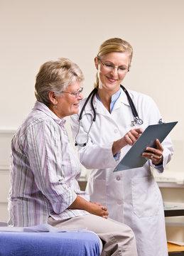 Doctor explaining medical chart to senior woman