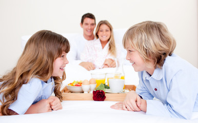Cheerful family having breakfast sitting on bed