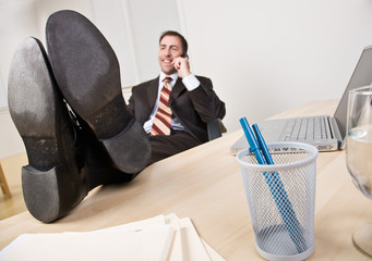 Businessman talking on telephone with feet up