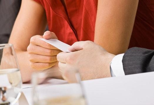 Businesswoman handing co-worker her business card