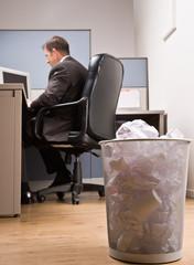 Businessman at desk and trash basket