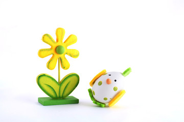 Easter simbol yellow wooden flower and white egg as chicken toy