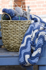 Blue wool and knitting needles in a wicker basket