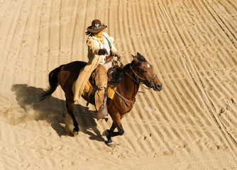 Wall Mural - Cowboy riding a horse at full gallop shooting a gun