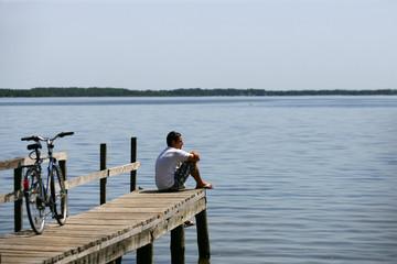 Homme assis au bord d'un lac