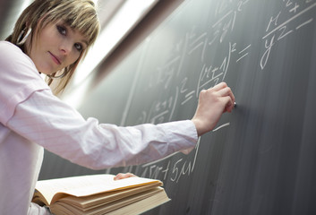 pretty college student/young teacher in front of a chalkboard