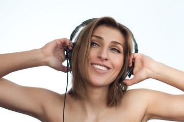 Girl listening music holding large headphones