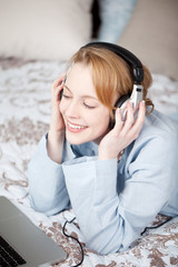 junge frau hört im schlafzimmer musik