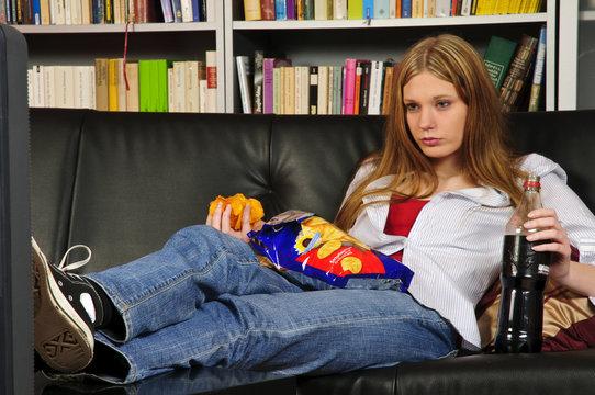 Mädchen gammelt faul auf dem Sofa vor TV