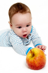 Portrait of the little boy with an apple on a light background