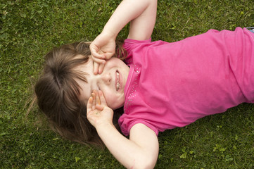 little girl laying in grass