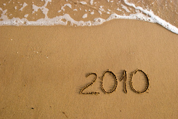 Year 2010 written on the sand