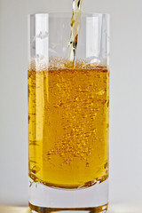 Amber liquid being poured into drinking glass