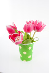 pink tulips in a green dotted vase isolated over white
