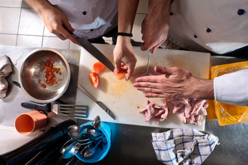 Two chefs cut the tomatoes and chicken in the kitchen
