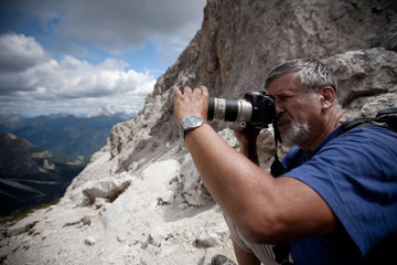 handsome senior male photographer in high mountain setting takin