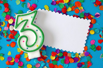Number three birthday candle on blue background