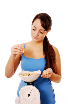 Young woman weighing bowl of cereal