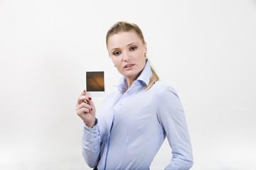 Beautitul young woman holding blank Polaroid