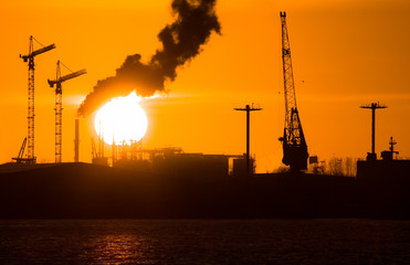 Industry silhouettes, pollution and big sun