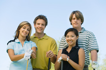 two couples of golfers posing on golf course (portrait)