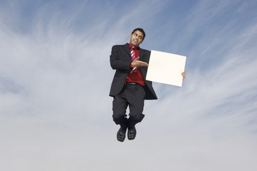 business man jumping with blank sign outdoors