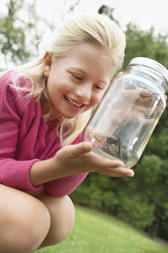 girl looking at grasshopper in jar