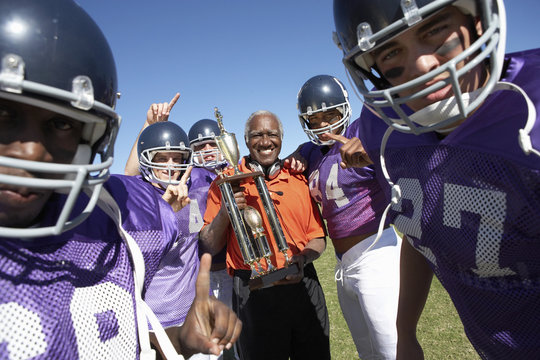 football coach and players holding trophy on field portrait (portrait)