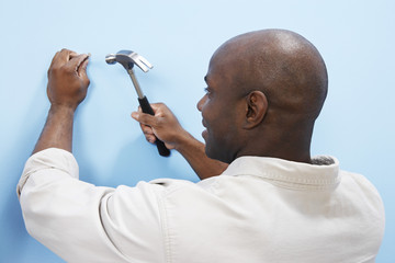man hammering nail into wall back view
