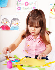 Child with  paper and glue in preschool. Child care.