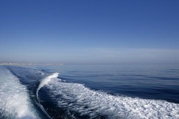 Blue sea ocean with boat wake, prop wash foam