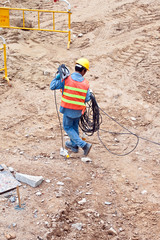 building worker at the building sitecarrying an electrical cable
