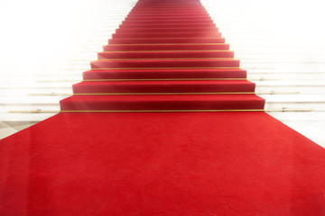 Staircase with red carpet, illuminated by light