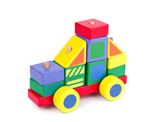 Toy car made of colorful wooden blocks on white background