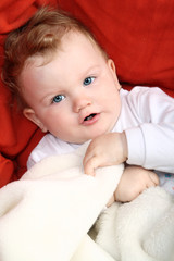 Baby girl lying on red sofa holding white blanket