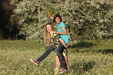 Two beautiful young women piggy- backing in blooming meadow