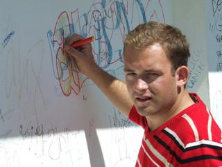 rapaz escrevendo em parede
