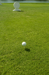 Golf course with golf ball and small monument