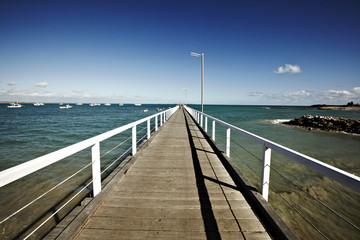 wooden walkway stretching toward the ocean on a sunny day