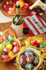 Easter eggs wine and ornaments on table