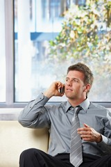 Businessman calling on sofa with gesture