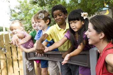 Preschool children playing on playground with teacher