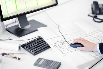 Schreibtisch eines Architekten mit Plan und Taschenrechner