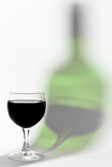 Red wine glass and bottle reflex