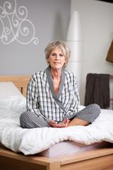 ältere frau sitzt entspannt auf dem bett