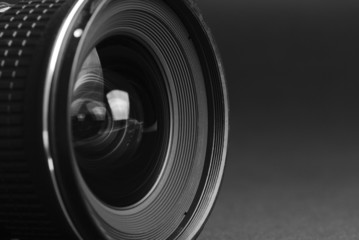 Close-up of a camera lens from the side, black background