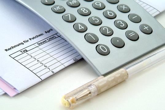 Rechnungen, Kugelschreiber und ein Taschenrechner.