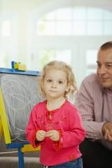 Dad watching daughter drawing
