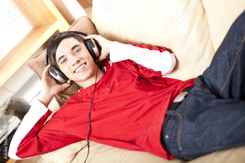 Lachender Teenager hört auf Sofa Musik - Boy listen mp3 music