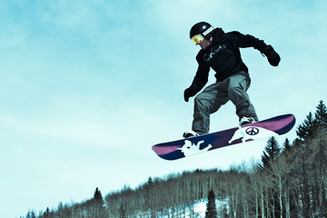 Vibrant Snowboarder catches air off jump